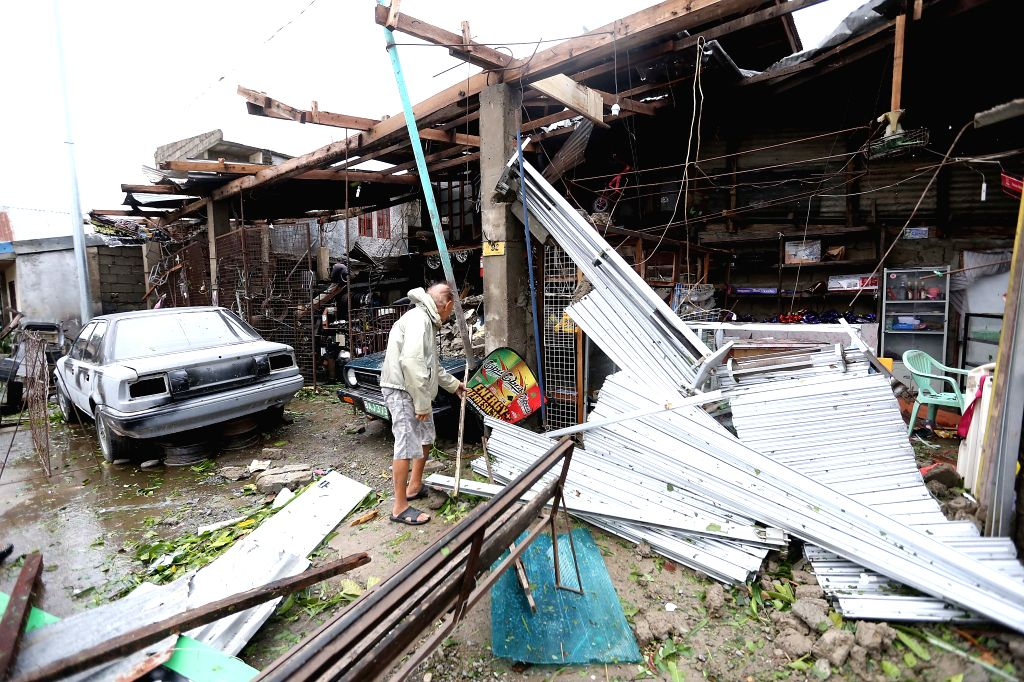 A resident clears the debris brought by the strong wind and heavy rain from Typhoon Haima in Cagayan Province, the Philippines, Oct. 20, 2016. At least ...