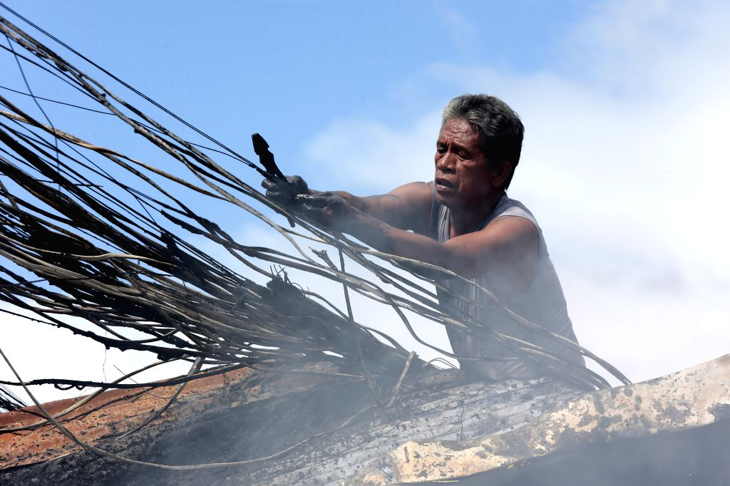 A resident collects copper wires that can be sold on a junkyard after a fire at a residential area in Mandaluyong City, the Philippines, Nov. 14, 2016. 2 ...