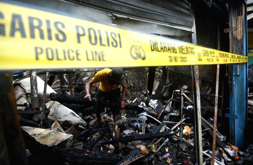 A resident looks for his belongings from a charred house after a fire at the densely populated area of Jelambar in Jakarta, Indonesia, Aug. 12, 2020.
