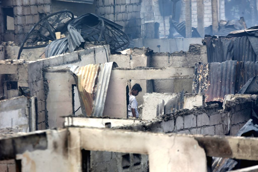 A resident looks for reuseable materials from his burnt home after a fire at a residential area in Mandaluyong City, the Philippines, Nov. 14, 2016. 2 ...