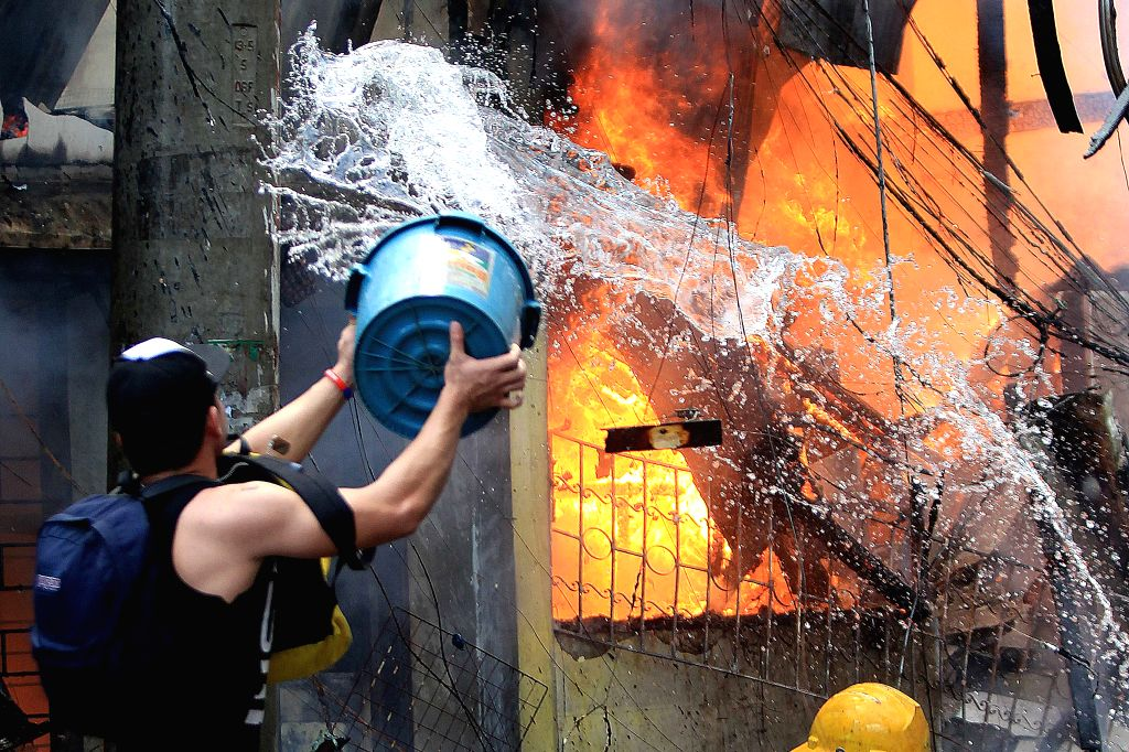 A resident throws a bucket of water as he tries to put out a fire at a slum area in Manila, the Philippines, Dec. 4, 2015. More than 500 shanties were razed in the ...