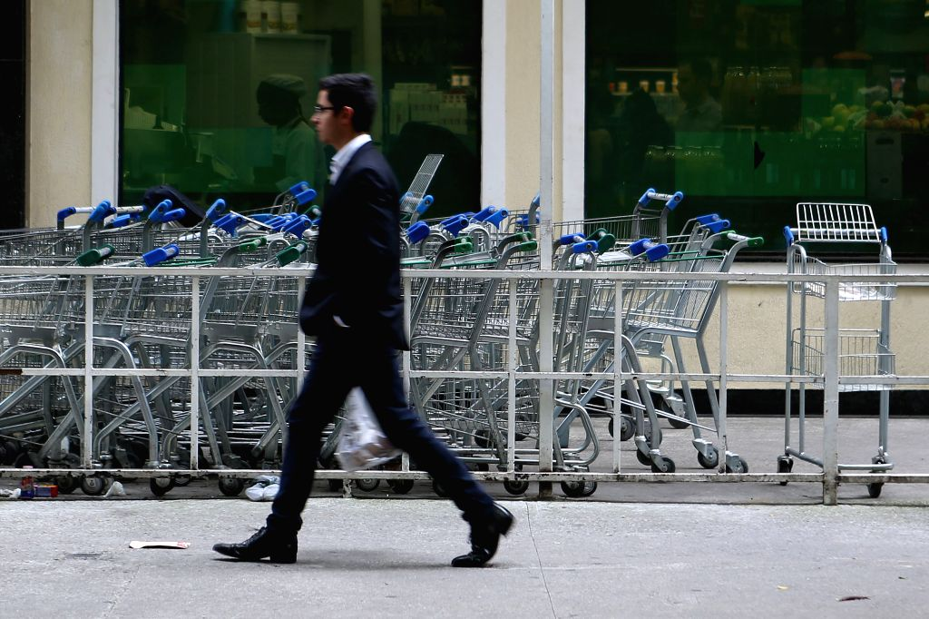 A resident walks past shopping carts, in Sao Paulo, Brazil, Dec. 9, 2015. The inflationary value in Brazil increased 10.49 percent in the las 12 months, after ...