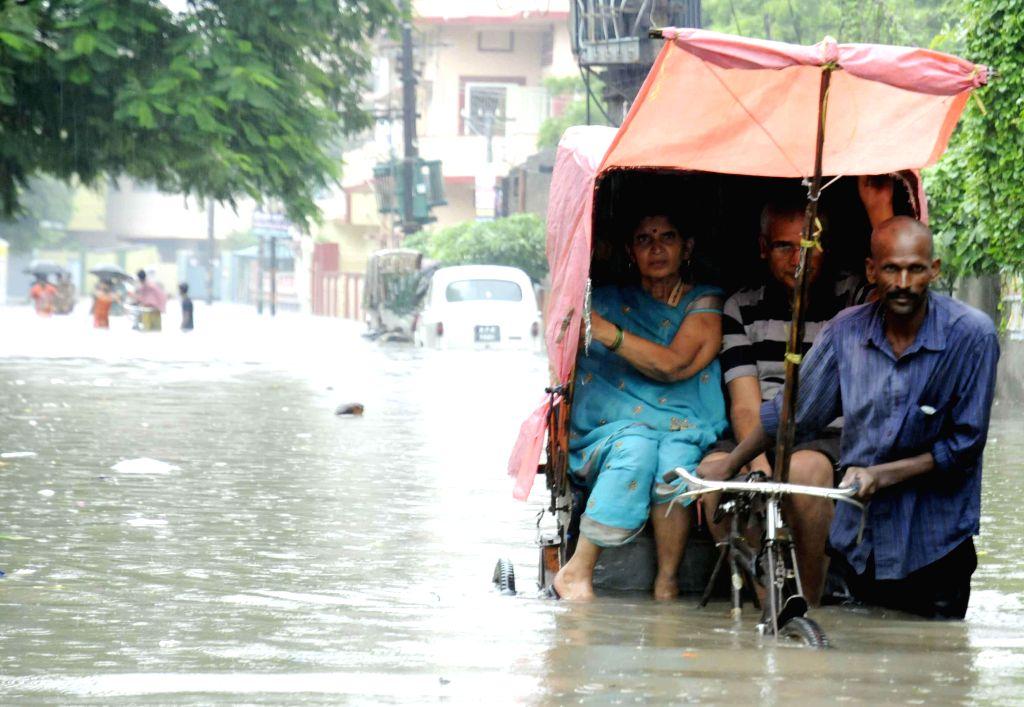 A rickshaw puller struggles through waterlogged streets of Patna on Aug 14, 2014.