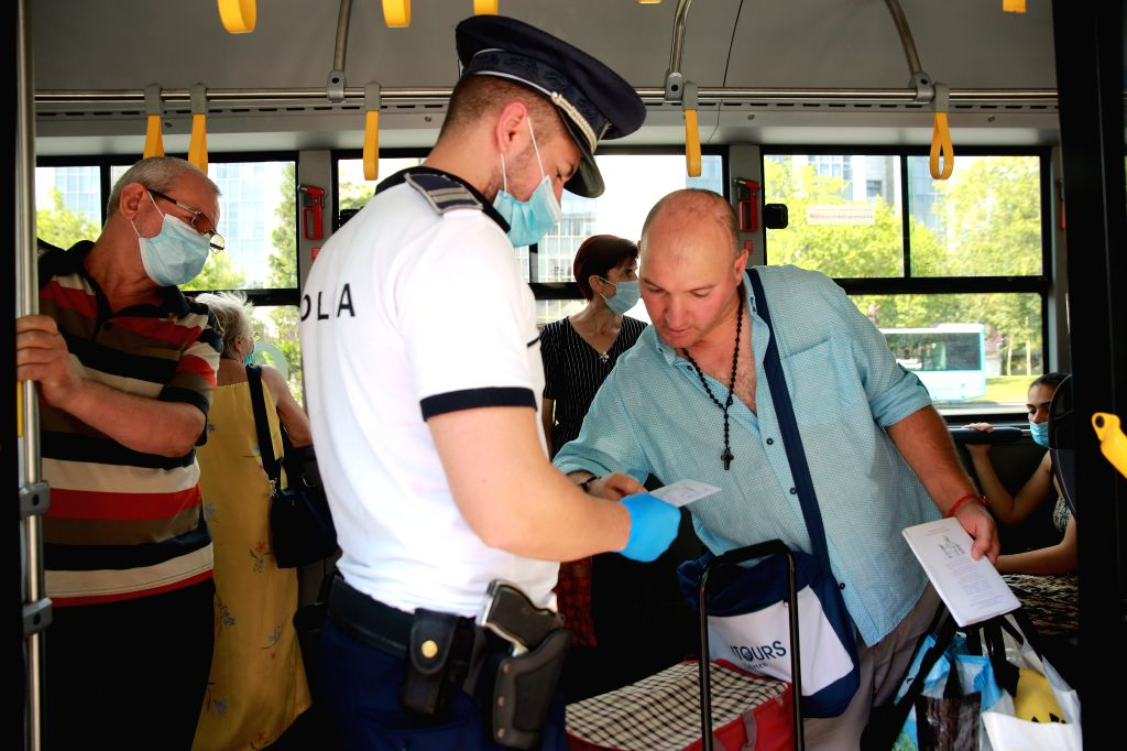 A Romanian Policeman checks the use of masks of passengers on a bus, in Bucharest, Romania, on August 1, 2020. Mask-wearing is being made mandatory in crowded ...
