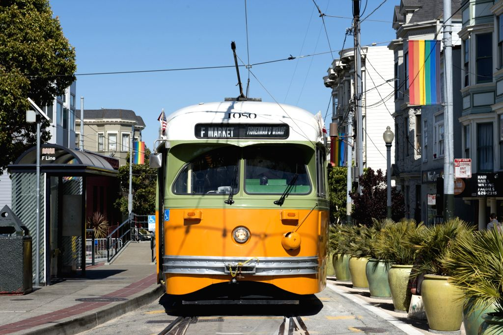 A San Francisco cable car transports sightseers through a residential area.