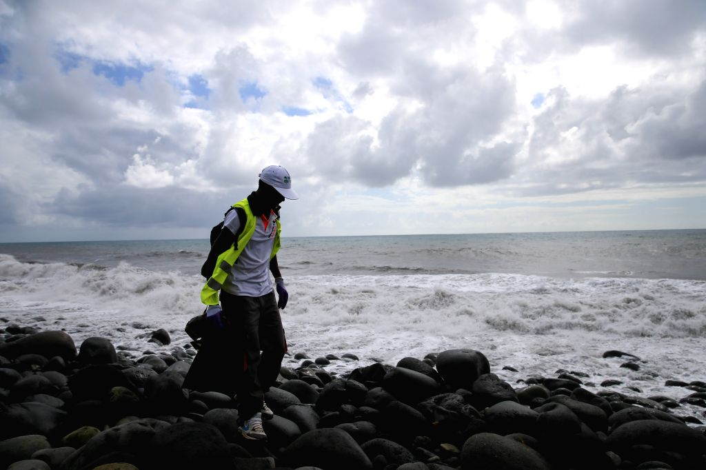 A searcher searches the Saint Andre beach, France's oversea island La Reunion, on Aug. 12, 2015. La Reunion authority Monday said that no clues related to the ...