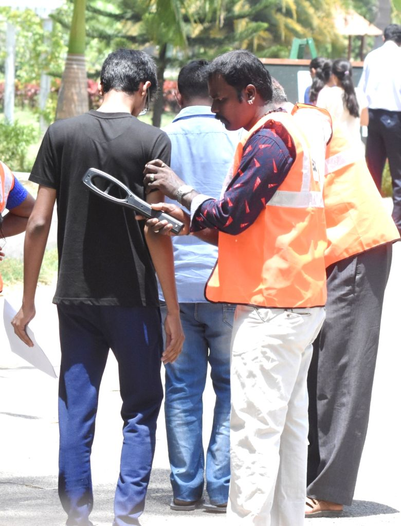 A security guard checks an applicant who has arrive for the National Eligibility cum Entrance Test NEET (UG) 2019 in Bengaluru, on May 5, 2019.