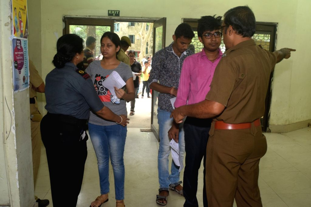 A security guard checks an applicant who has arrive for the Joint Entrance Examination (JEE) 2019 in Kolkata, on May 26, 2019.