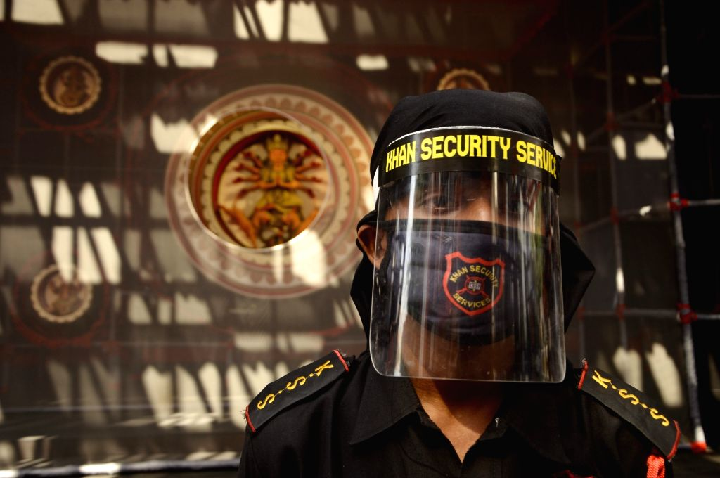 A security guard wearing a mask and a face shield stands guard at a community puja pandal ahead of Durga Puja celebrations, at Jodhpur Park in Kolkata on Oct 21, 2020.