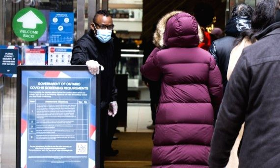 A security officer wearing a face mask checks customers' health screening results at the entrance of CF Toronto Eaton Center in Toronto, Canada, on March 8, 2021.