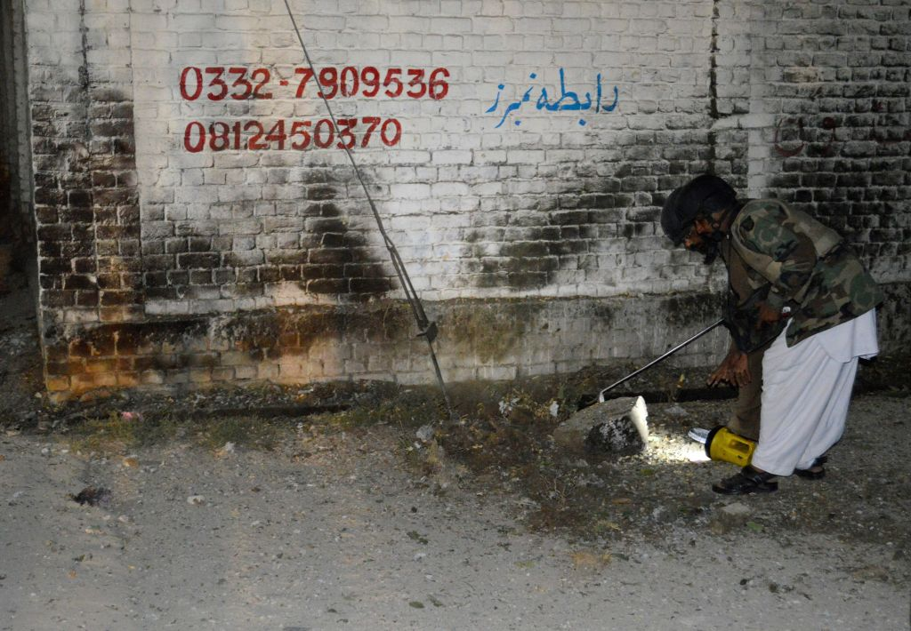 A security official checks an explosion site in Quetta, Pakistan, on Oct. 29, 2015. At least five people were killed and two others injured as a car struck an ...