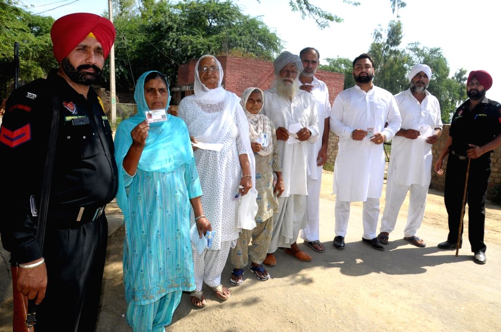 A security personnel stands guard as voters arrive to cast their votes during re-polling at the polling station number 123 of Amritsar parliamentary constituency after the Election ...