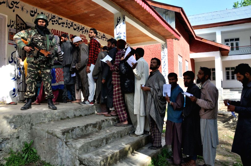 A security personnel stands guard as voters queue up to cast their votes for the fourth phase of 2019 Lok Sabha elections, at a polling station in Jammu and Kashmir's Kulgam on April 29, 2019.