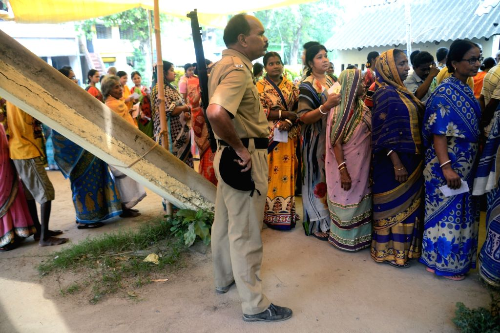A security personnel stands guard as women wait in queue to cast votes during the sixth phase of 2019 Lok Sabha polls, in West Bengal's Midnapore, on May 12, 2019.