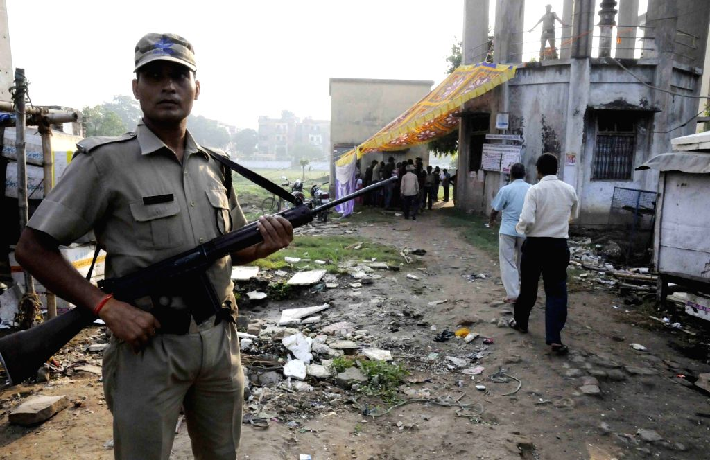 A security personnel stands guard at a polling booth during the third phase of Bihar assembly polls in Patna on Oct 28, 2015.