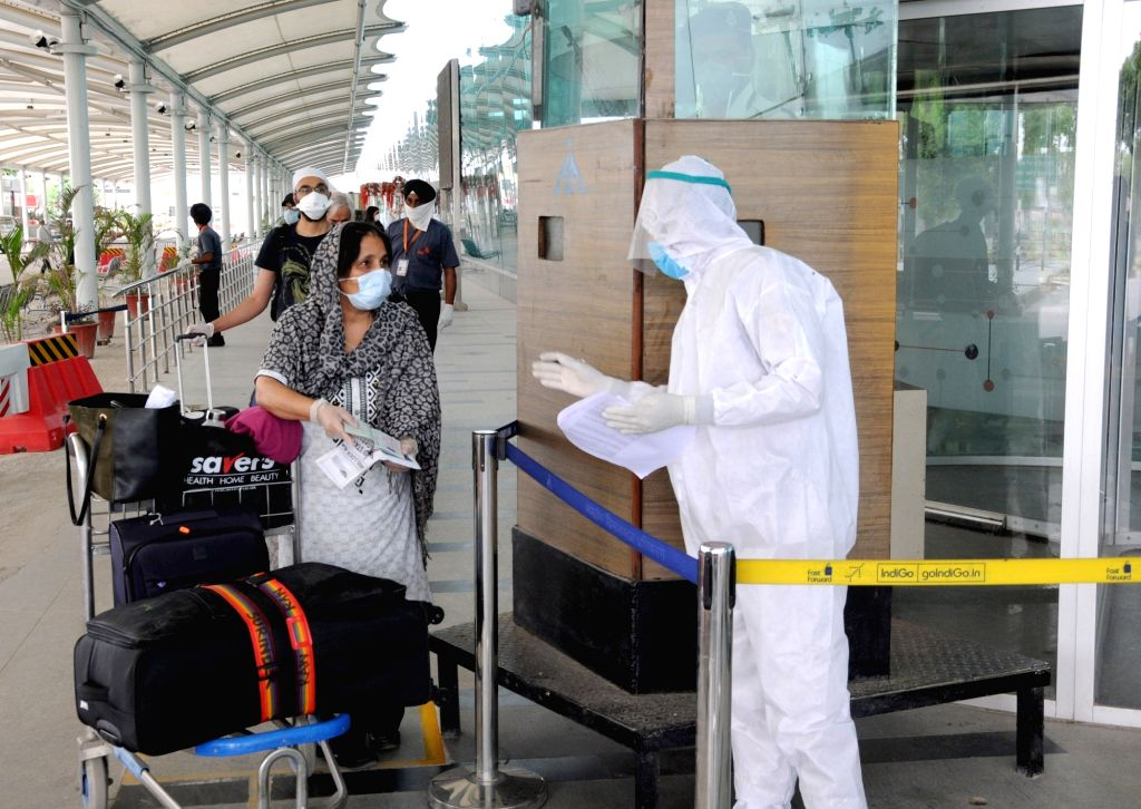 A security personnel wearing Personel Protective Equipment (PPE) suit checks the passports of British nationals before check-in for a special flight to London during the extended nationwide ...