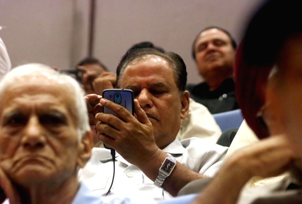A senior person looks at a mobile app launched by Delhi Lieutenant Governor Najeeb Jung for Senior Citizen during a programme on International Senior Citizen Day in New Delhi on Oct 1, ...