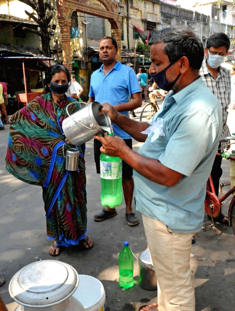 A shopkeeper busy attending customers wearing a mask on Day 5 of the 21-day countrywide lockdown imposed to contain the spread of novel coronavirus, in Kolkata on March 29, 2020.