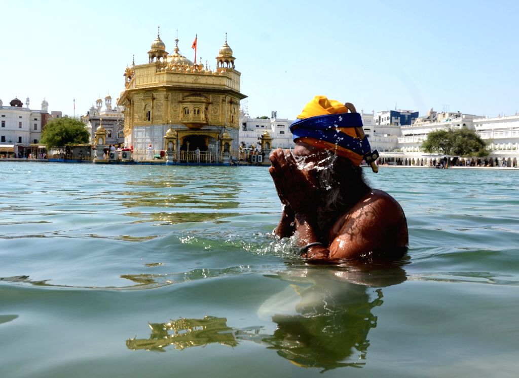 A Sikh devotee takes a dip in the holy sarovar (pond) at Golden Templeon the birth anniversary of Guru Amar Das third of the Ten Gurus of Sikhism in Amritsar, Tuesday, May 25, 2021.