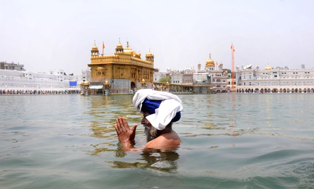 A Sikh devotee takes a dip in the sarovar of the Golden Temple on the occasion of Third Sikh Guru Amar Das birth anniversary in Amritsar on May 20, 2016.