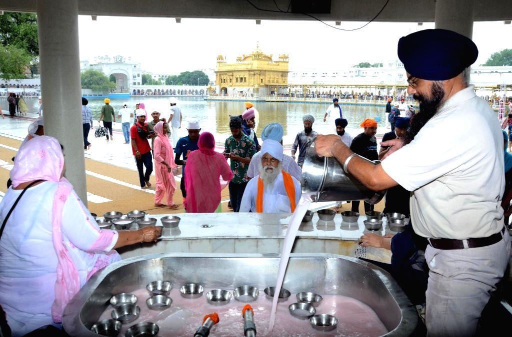 A Sikh volunteer prepares sweet water to distribute to devotees on the occasion of the 415th Sikh Guru Arjan Dev's martyrdom day at the Golden Temple in Amritsar on Monday 14 June,2021. - Guru Arjan Dev