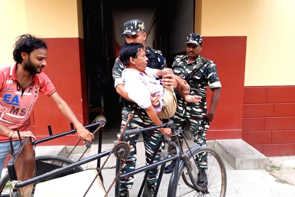 A soldier carries a physically challenged man, who came to cast vote during the last phase of 2019 Lok Sabha polls, in Kolkata, on May 19, 2019.