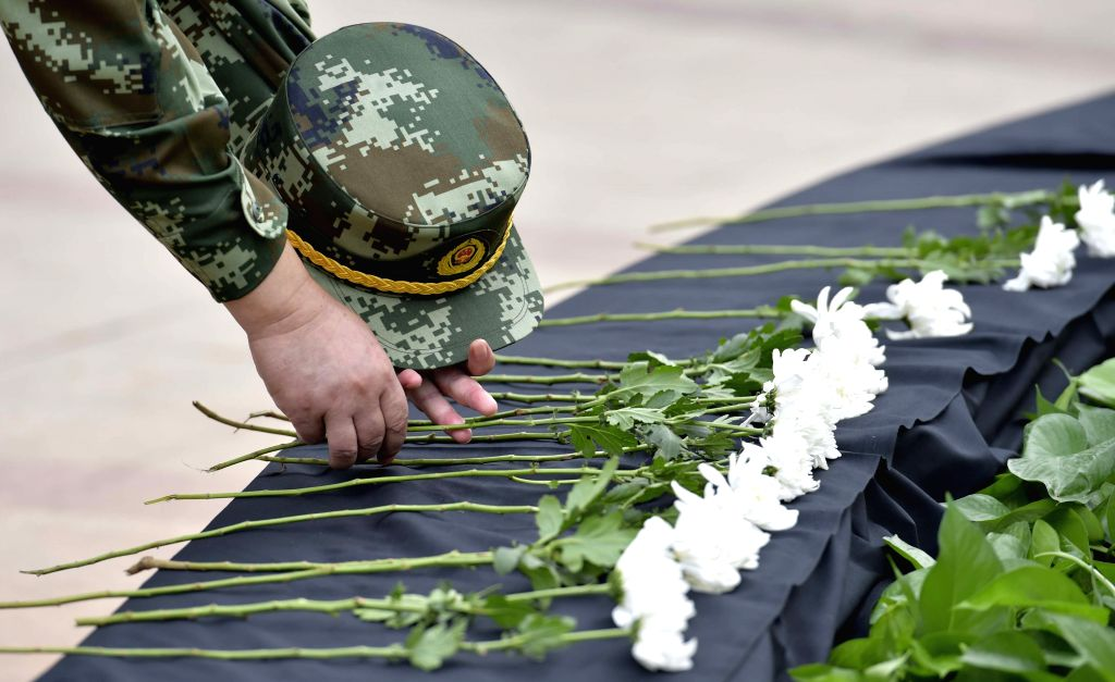 A soldier lays a flower during a mourning ceremony held for the victims of the massive warehouse explosions, at a street park in the Binhai New Area of Tianjin, ...
