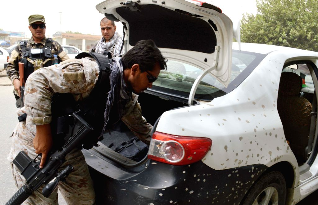 A soldier searches a vehicle at a checkpoint in Kunduz Province, north Afghanistan, Aug. 9, 2015. About 22 people were killed in a suicide car bombing in Kunduz late ...