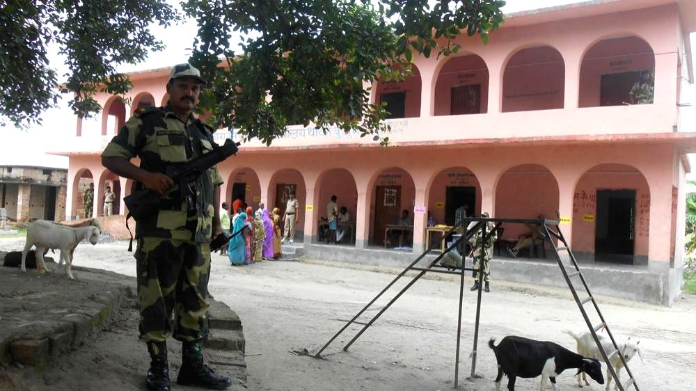 A soldier stands guard at a polling booth during by-elections in Saran Lok Sabha constituency of Bihar on Aug 21, 2014.