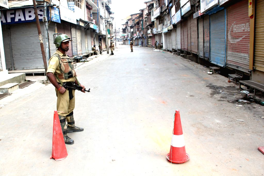 A soldier stands guard on a Srinagar road as curfew continued in parts of the Kashmir Valley amid fears of more violence where 21 people have been killed in clashes with police and ...