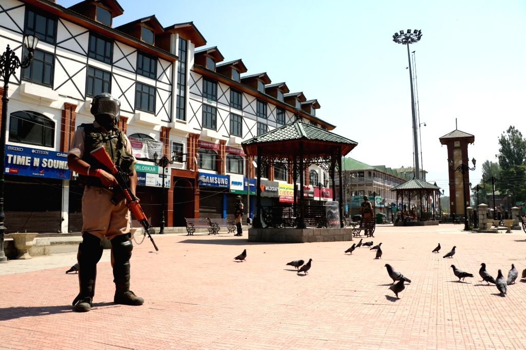 A soldier stands guard on a Srinagar road as authorities imposed valley-wide restrictions and curfew for the third consecutive day to prevent a separatist-called march to Tral, the hometown ...