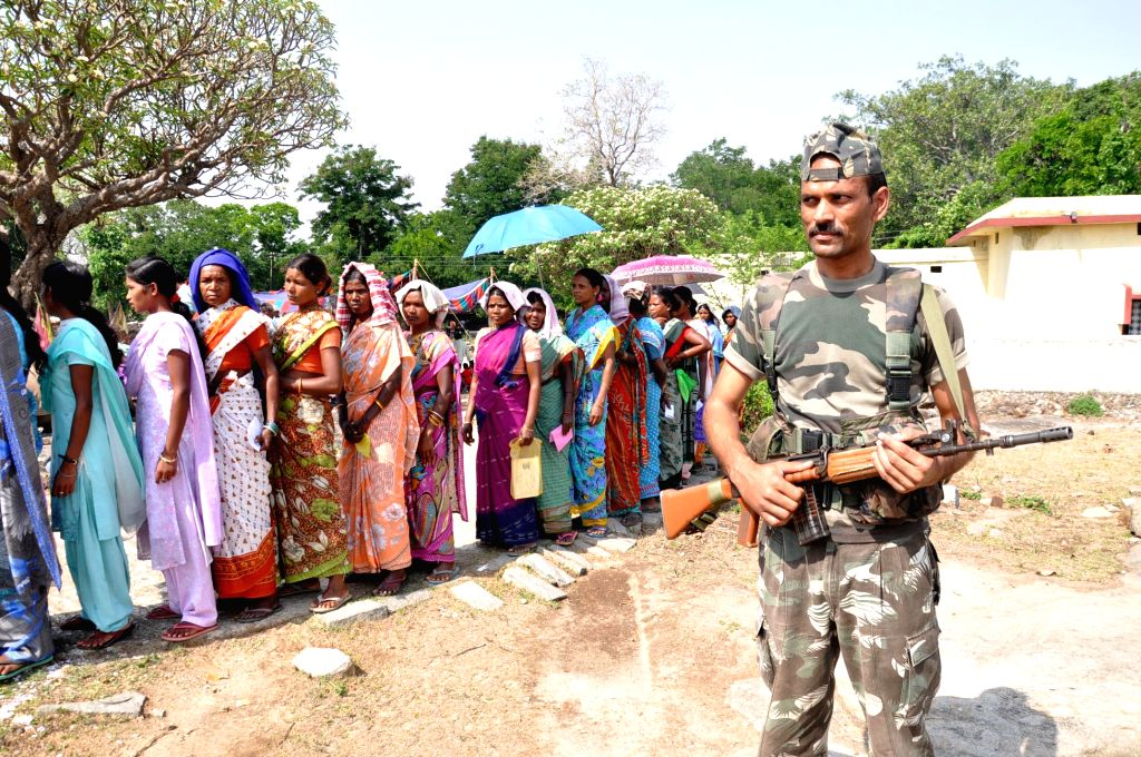 A soldier stands on guard as women queue-up to cast their votes at a polling booth during the fifth phase of  2014 Lok Sabha Polls in Khunti of Jharkhand on April 17, 2014. Elections are being held ..