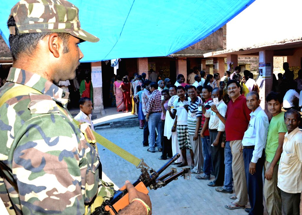 A soldier stands on guard as women queue-up to cast their votes at a polling booth during the fifth phase of  2014 Lok Sabha Polls in Patna on April 17, 2014. Elections are being held in 117 ...