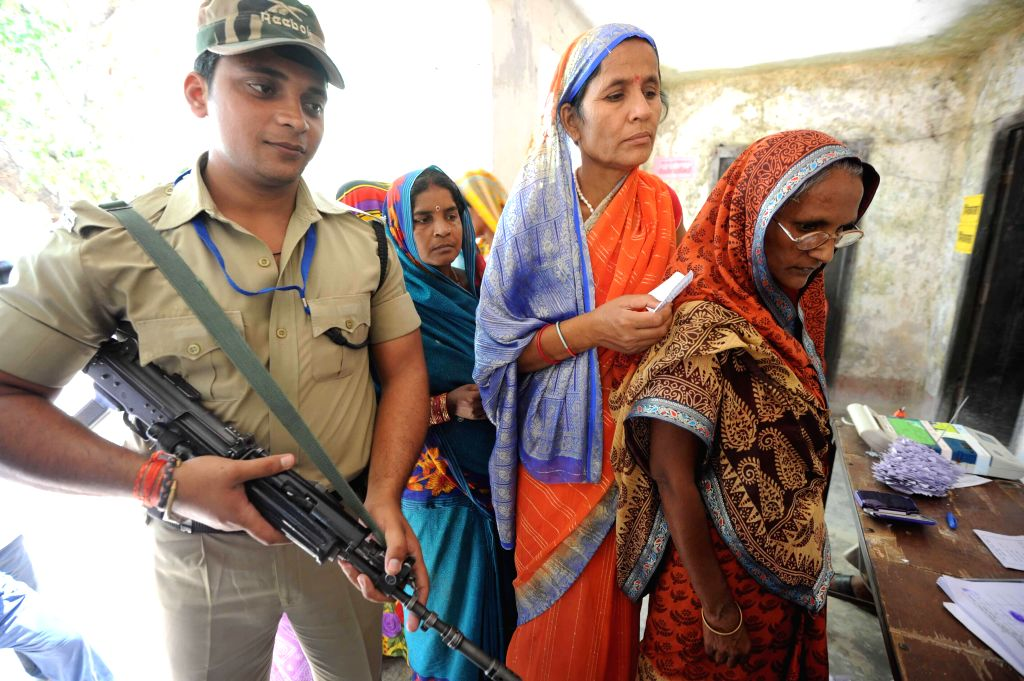 A soldier stands on guard as women queue-up to cast their votes at a polling booth during the ninth phase of 2014 Lok Sabha Polls in Vaishali district of Bihar on May 12, 2014.