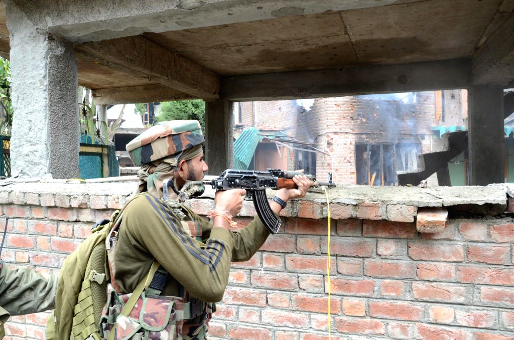 A soldier takes position during an encounter with militants in Hanjan village of Rajpora in Jammu and Kashmir's Pulwama district on Sept 2, 2014. Three militants were killed in the encounter.