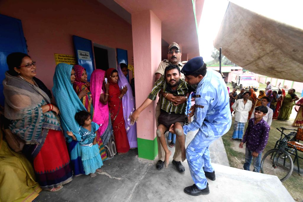 A specially-abled voter being assisted to a polling station by security personnel to cast vote for the fourth phase of 2019 Lok Sabha elections in Bihar's Samastipur, on April 29, 2019.