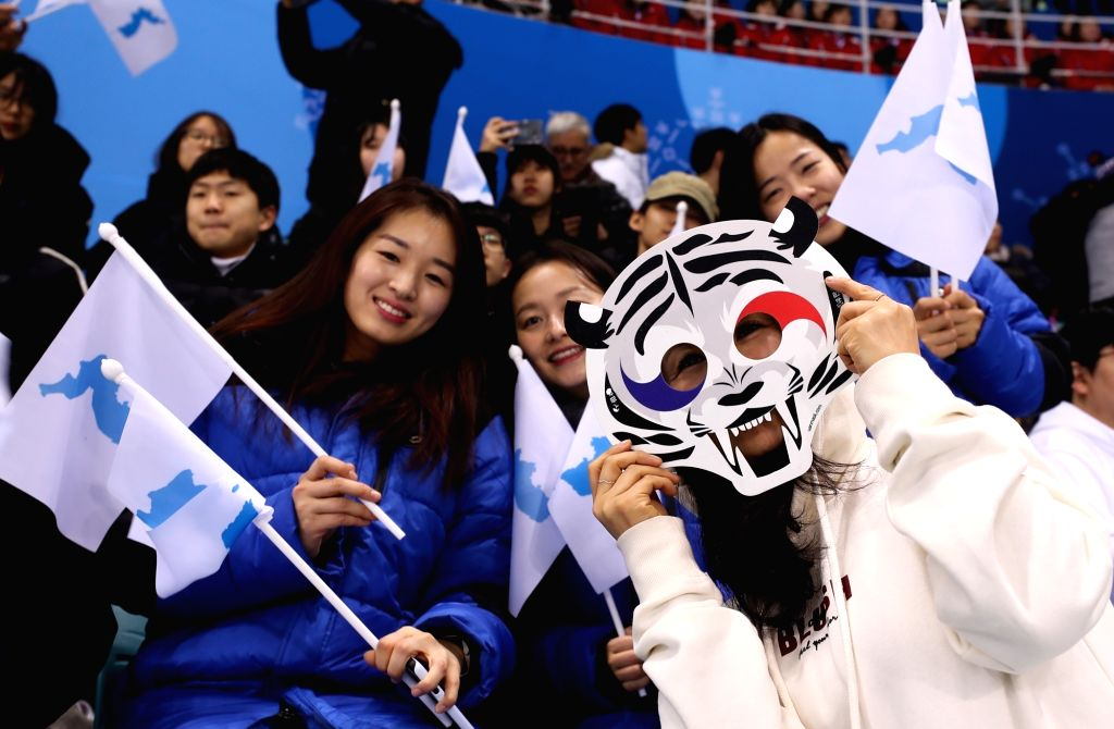 A spectator wears a mask of Soohorang, the official mascot of the 2018 Winter Olympics, while cheering for the joint Korean women's hockey team that faced Sweden in the women's hockey ...