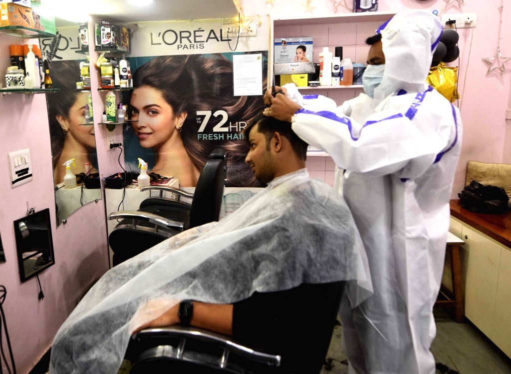 A staff attends a customer at a salon that reopened after the COVID-19 lockdown began in a phased manner, in Mumbai on Monday, 07June  2021 (Photo : Sandeep Mahankal/ IANS)