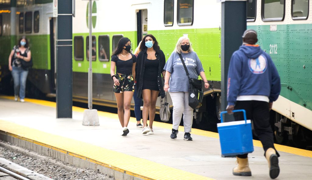 A staff member (1st L) of VIA Rail Canada hands over a new face mask to a passenger at Union Station in Toronto, Canada, on June 23, 2020. Passengers of Canada's ...