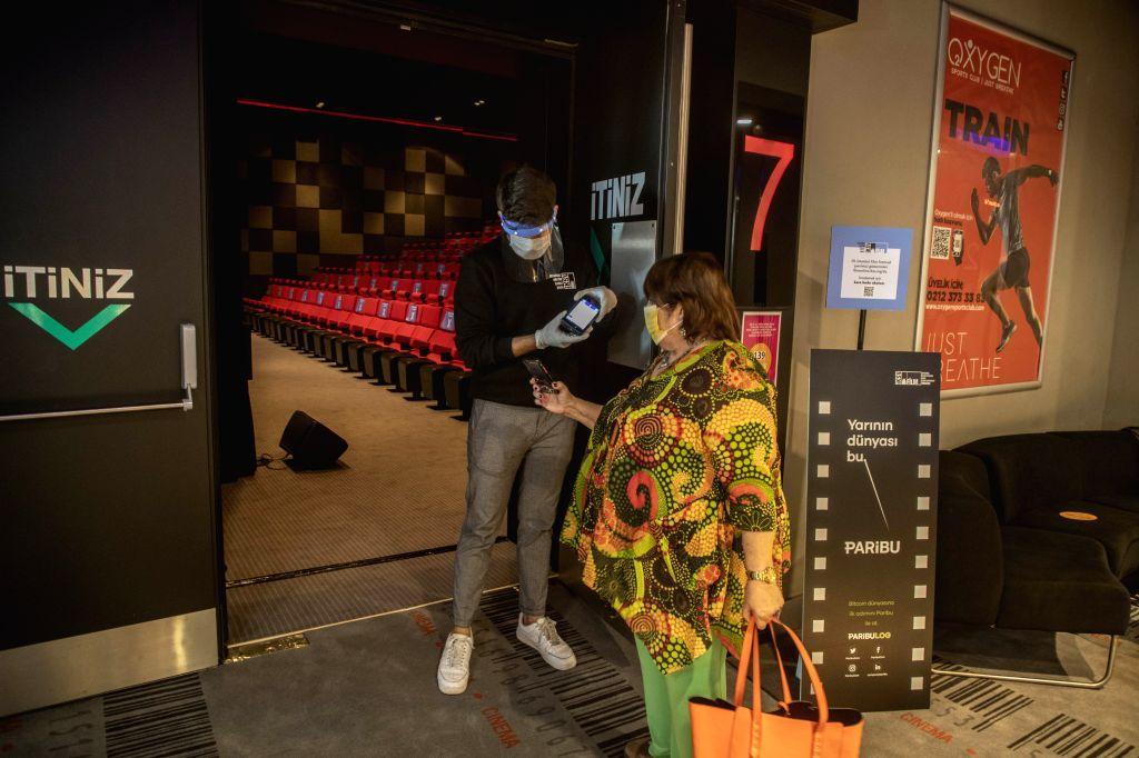 A staff member checks an e-ticket for a film in Istanbul, Turkey, on Oct. 13, 2020. Due to the COVID-19 pandemic, the Istanbul Film Festival, one of the most ...