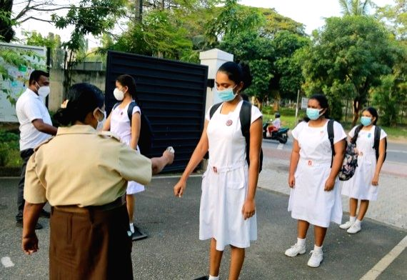 A staff member checks the body temperature of students at the entrance to a girls' school in Colombo, Sri Lanka, Jan. 25, 2021.