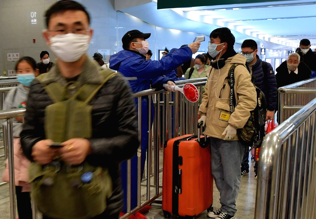 A staff member checks the body temperature of passengers at the Nanchang Railway Station in Nanchang, east China's Jiangxi Province, Feb. 6, 2020. The station has ...