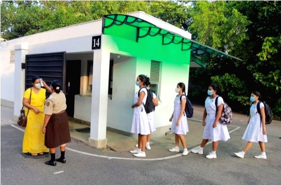 A staff member checks the body temperature of a teacher at the entrance to a girls' school in Colombo, Sri Lanka, Jan. 25, 2021.