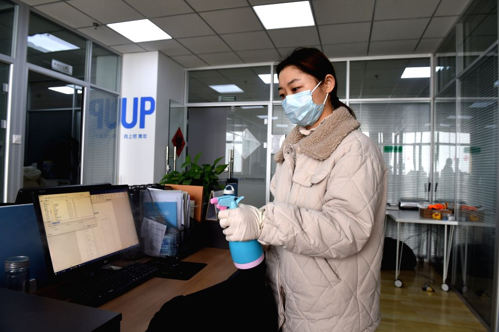 A staff member disinfects the working area in a company in Hefei National High-tech Industry Development Zone in Hefei, east China's Anhui Province, Feb. 12, 2020. ...