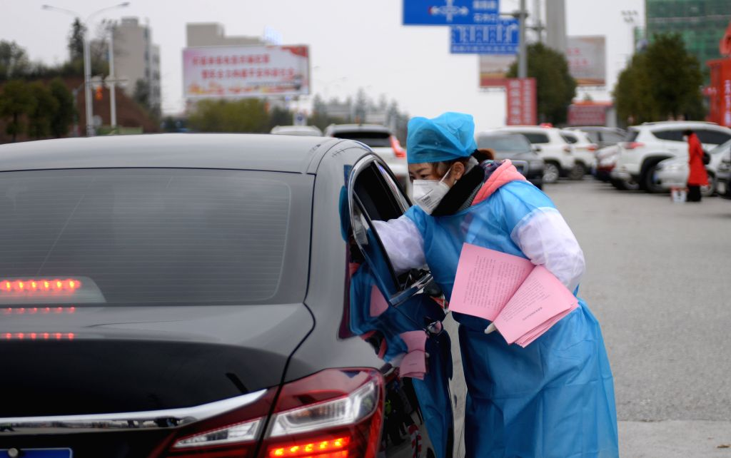 A staff member distributes leaflets on the prevention and control of the novel coronavirus to drivers and passengers at the Xinhua exit of Louhuai Expressway in ...