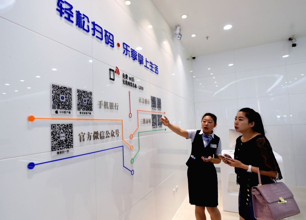 A staff member introduces to a customer the way of getting served through APP at the Guigu Branch of the Bank of Lanzhou in Lanzhou, capital of northwest China's ...