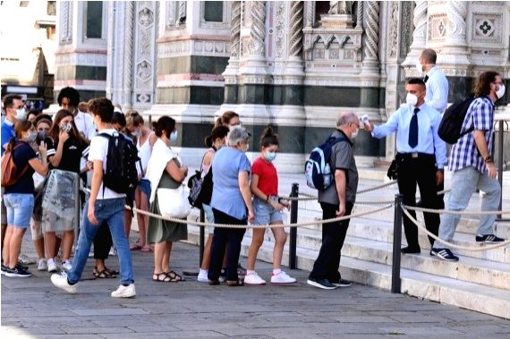 A staff member measures a visitor's temperature at Cattedrale di Santa Maria del Fiore in Florence, Italy, on Sept. 4, 2020.