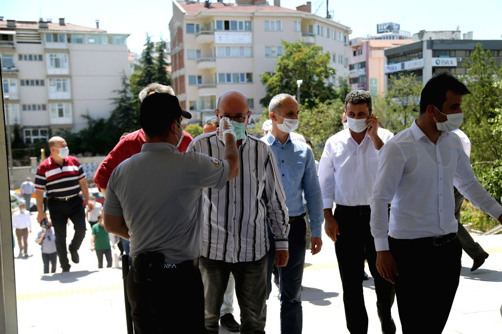 A staff member measures people's body temperature before they attend the Friday prayers in Ankara, Turkey, on Aug. 7, 2020. Turkey reported 1,185 new COVID-19 cases ... - Fahrettin Koca