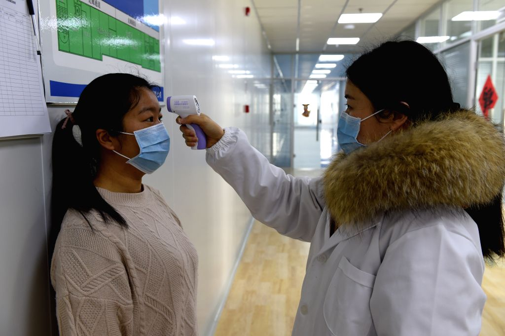 A staff member receives body temperature check in a company in Hefei National High-tech Industry Development Zone in Hefei, east China's Anhui Province, Feb. 12, ...