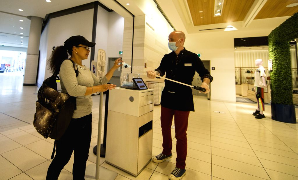 A staff member wearing a face mask offers a face mask to a customer at CF Toronto Eaton Center in Toronto, Canada, on June 24, 2020. The City of Toronto moved to ...
